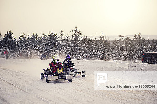Boys enjoying go-carts racing on snow covered field against sky