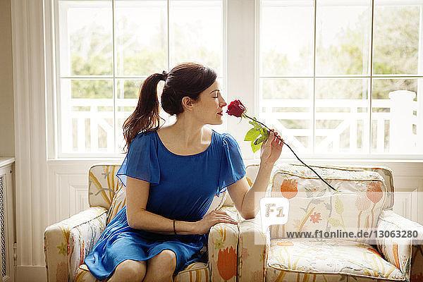 Frau riecht an roter Rose  während sie zu Hause auf einem Sessel sitzt