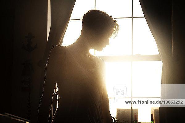 Frau steht zu Hause am Fenster