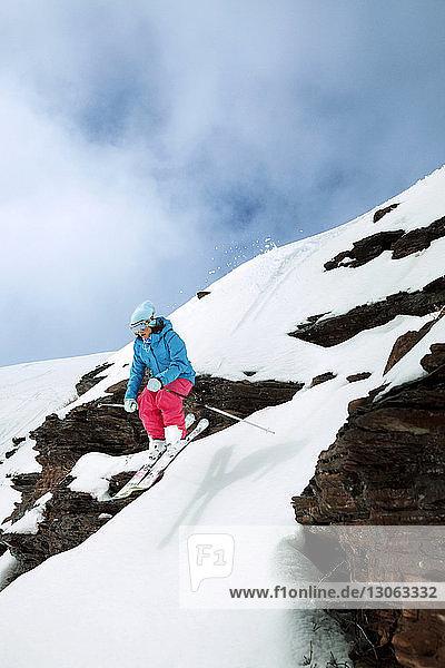 Female skier skiing downhill on mountain