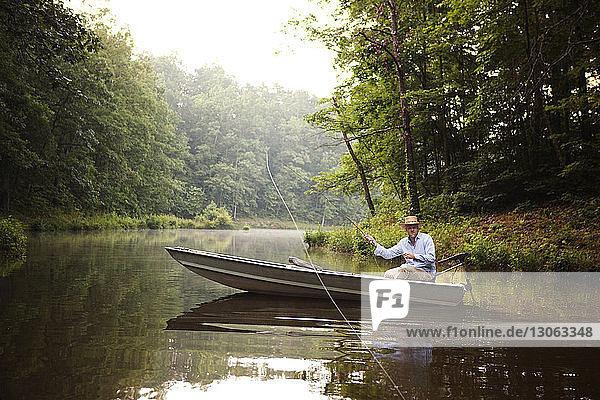 Man casting fishing rod while fishing in lake