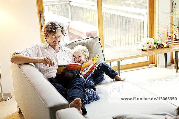 Glückliche Vater und Sohn lesen Buch  während sie zu Hause auf dem Sofa sitzen