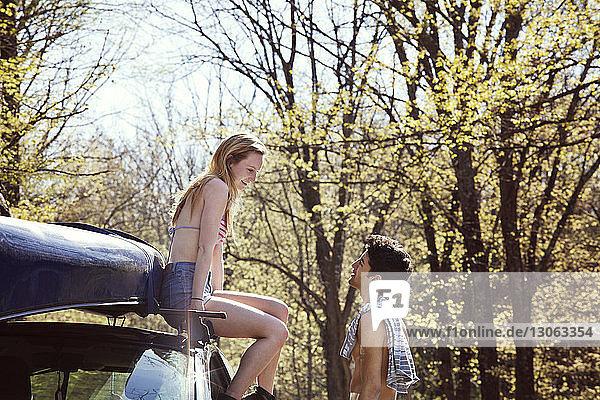 Man talking with woman sitting on car