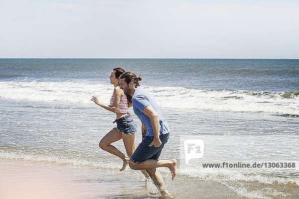 Side view of couple running on shore at beach during summer vacation