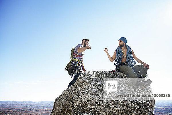 Freunde machen einen Faustschlag  während sie auf einem Felsen gegen den klaren Himmel sitzen