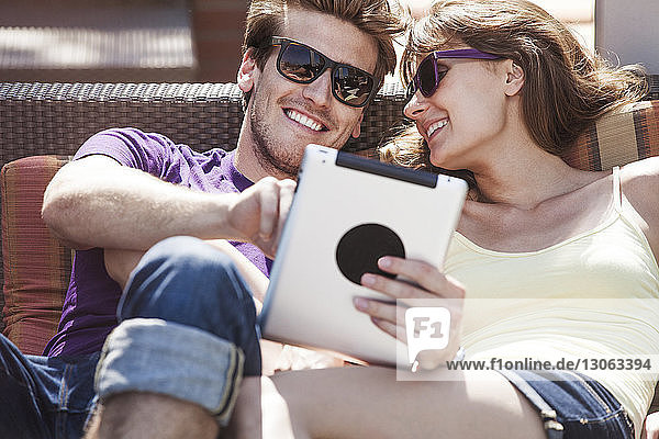 Glückliches Paar benutzt Tablette  während es auf dem Sofa im Hinterhof sitzt