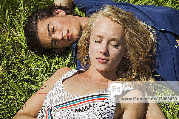 High angle view of couple relaxing on grassy filed