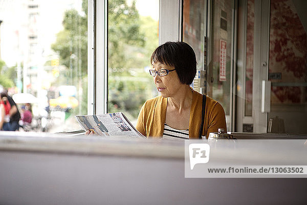 Woman reading newspaper while sitting in restaurant