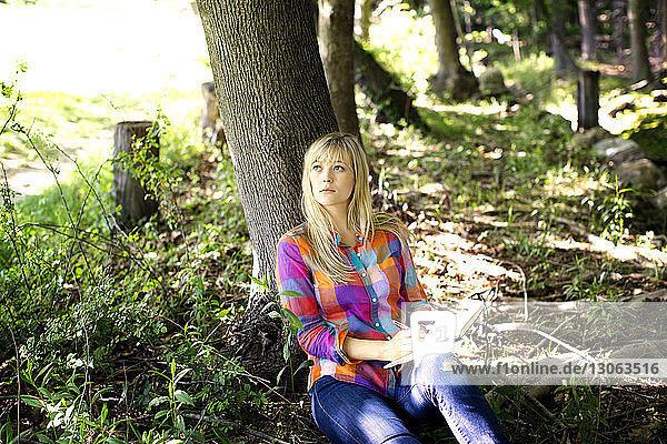 Frau schaut auf  während sie im Wald am Baumstamm sitzt