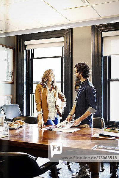 Geschäftsleute sprechen  während sie im Büro am Schreibtisch stehen