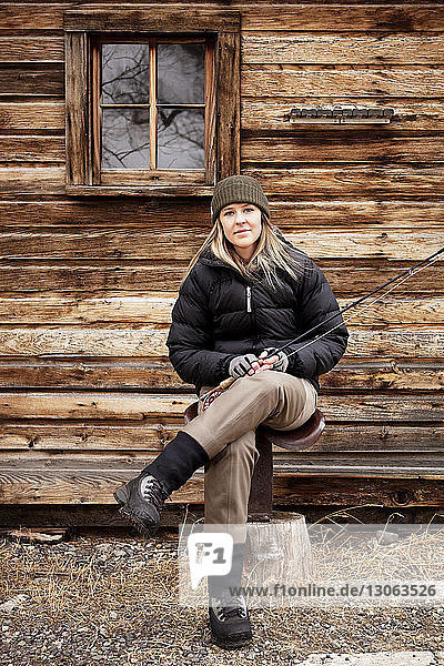 Portrait of confident woman holding fishing rod against house