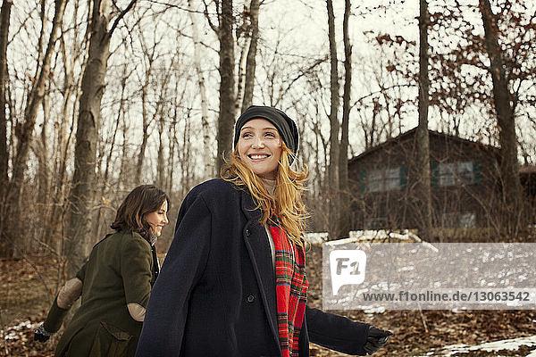 Glückliche Freunde spazieren im Winter im Wald