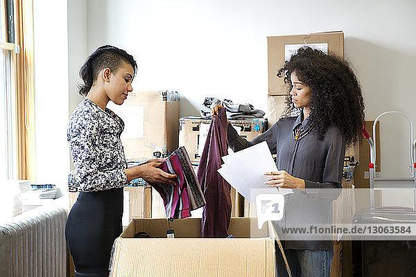 Arbeiter untersuchen Kleidung im Büro