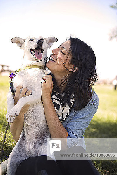 Happy woman with playful dog at park against sky