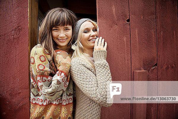 Porträt von glücklichen Freunden  die an einer Holzbohle stehen