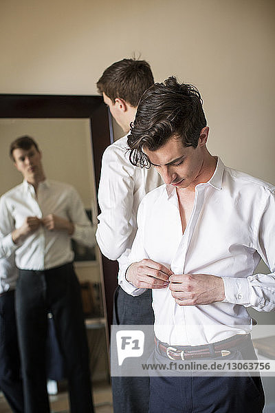Gay men getting dressed at home