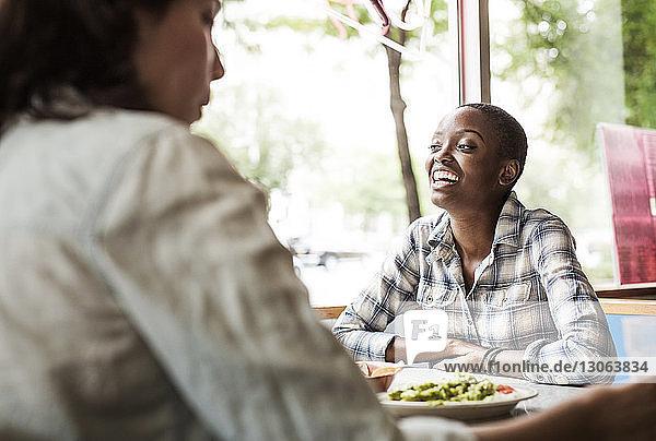 Lächelnde Frau sitzt mit Freunden im Restaurant