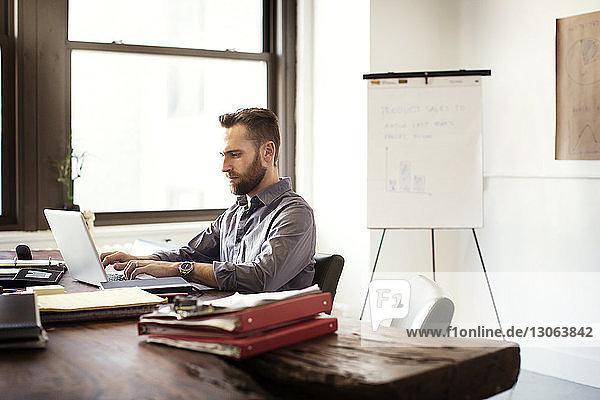 Mann arbeitet am Laptop-Computer  während er im Büro am Schreibtisch sitzt