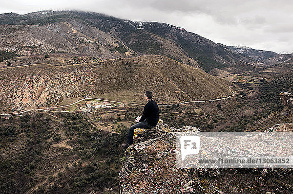 Rear view of man sitting on mountain cliff