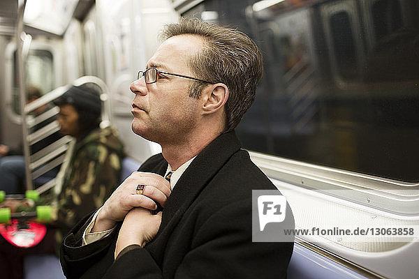 Businessman adjusting necktie in train