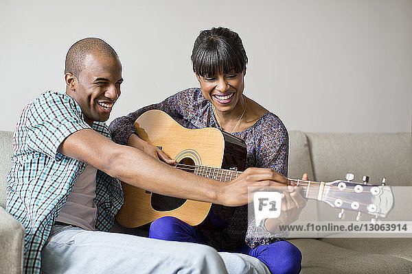 Man teaching guitar to girlfriend while sitting on sofa at home