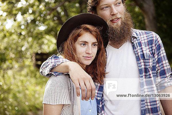 Paar mit Arm  das im Wald steht und dabei wegschaut