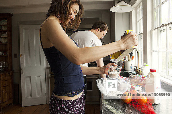 Couple preparing breakfast while standing at home