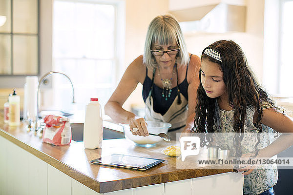Granddaughter and grandmother preparing food while looking in tablet computer at kitchen