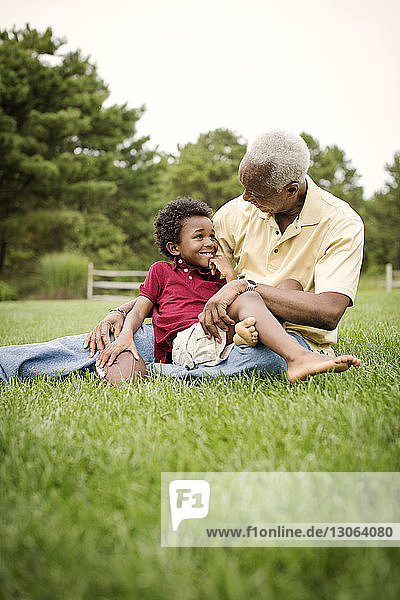 Grandfather and grandson talking while sitting on grassy field in backyard