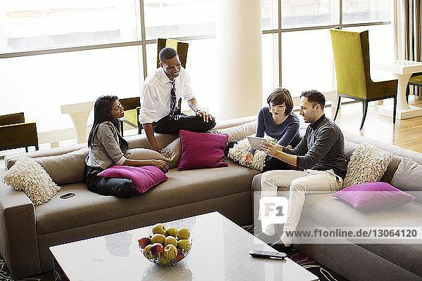 Schrägansicht von Kollegen  die im Büro auf dem Sofa sitzen und sich unterhalten