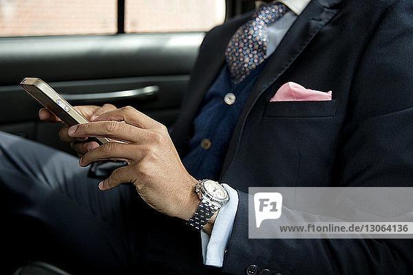 Ausgeschnittenes Bild eines Geschäftsmannes  der ein Mobiltelefon benutzt  während er im Auto sitzt
