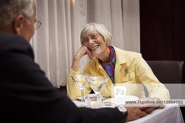 Ältere Frau schaut den Mann an  während sie im Restaurant sitzt