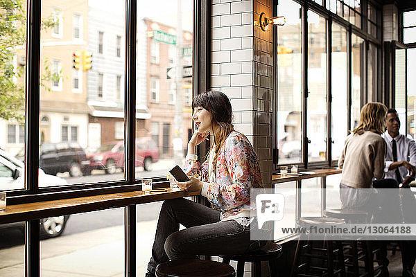 Frau hält Buch  während sie in der Bar sitzt