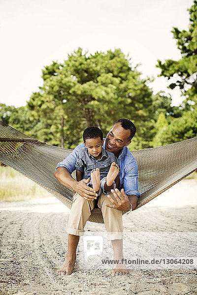Happy father and son relaxing on hammock in backyard