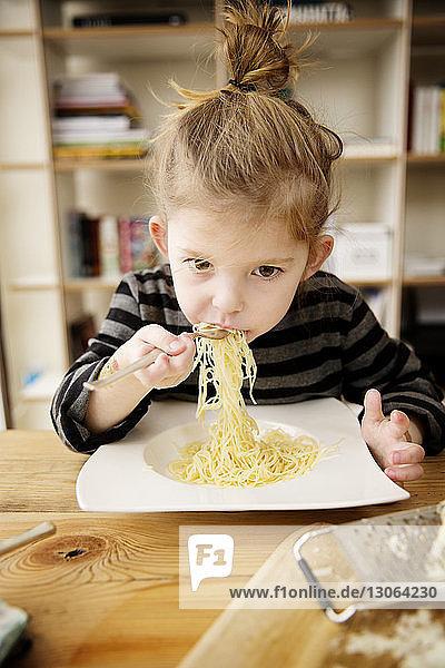 Süßes Mädchen isst zu Hause Nudeln bei Tisch