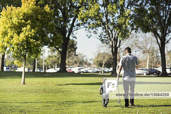 Rückansicht von Vater und Sohn beim Spaziergang auf einem Grasfeld
