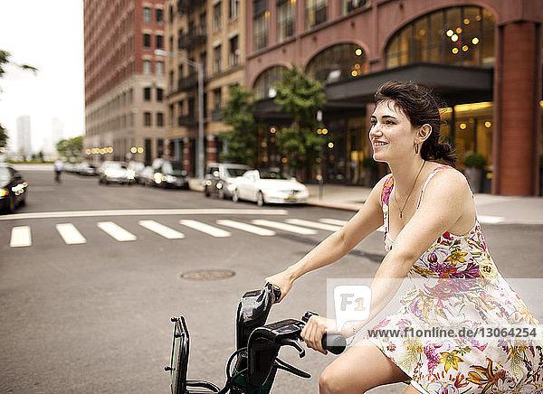 Glückliche Fahrrad fahrende Frau in der Stadt