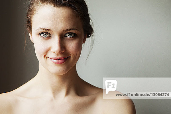 Portrait of smiling woman standing against wall at home