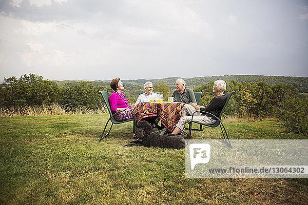 Ältere Freunde sitzen am Frühstückstisch im Rasen gegen den Himmel