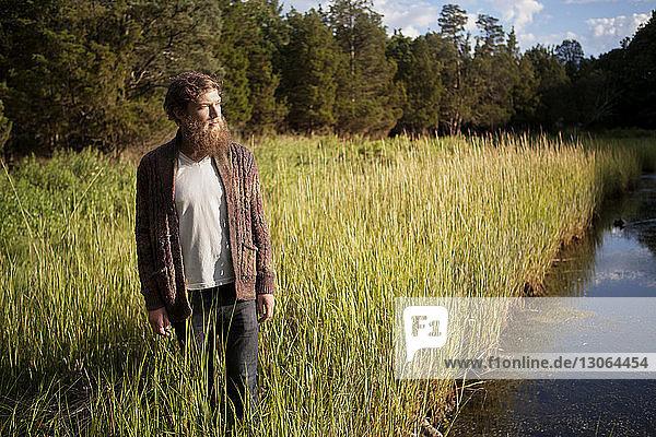 Mann schaut weg  während er auf einem Grasfeld vor einem See im Wald steht