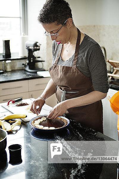 Woman placing banana slices on chocolate tart