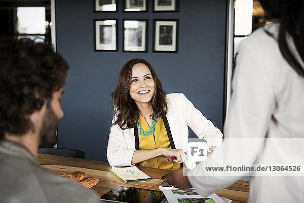 Lächelnde Geschäftsfrau sieht Amtskollegin an