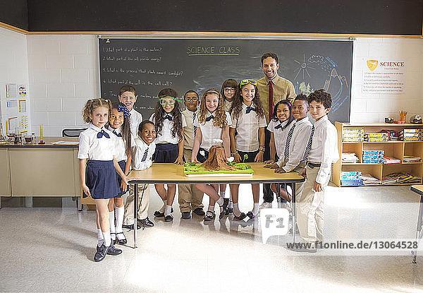 Porträt von Schülern mit am Schreibtisch stehendem Lehrer im Klassenzimmer