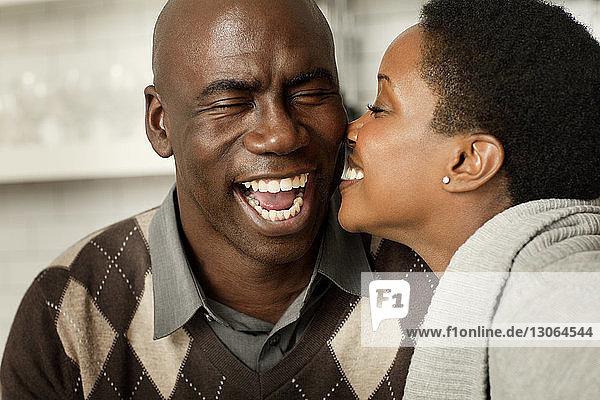 Glückliche Frau küsst Mann  während sie in der Küche sitzt