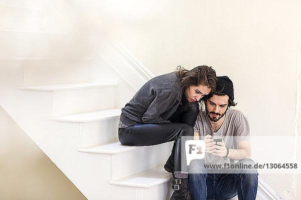 Ehepaar betrachtet Smartphone  während es auf der Treppe sitzt