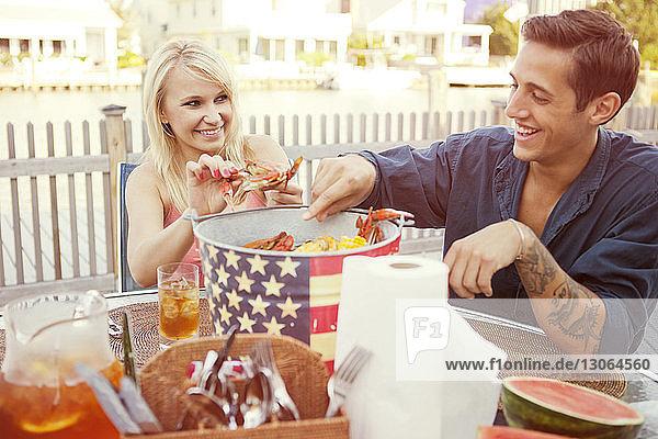 Glückliches Paar entfernt Krabben aus dem Container  während es am Tisch im Hinterhof sitzt