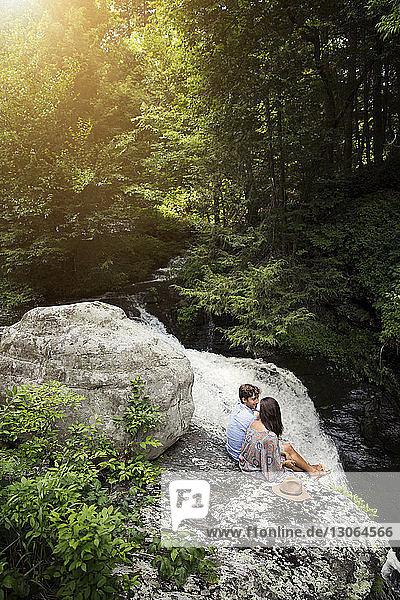 Hochwinkelaufnahme eines Paares  das auf Felsen am Wasserfall im Wald sitzt