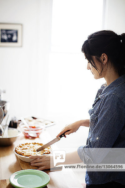 Side view of woman cutting pie while standing by kitchen counter at home
