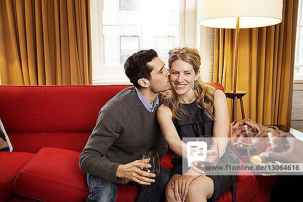 Glücklicher Mann küsst Freundin mit Weinglas