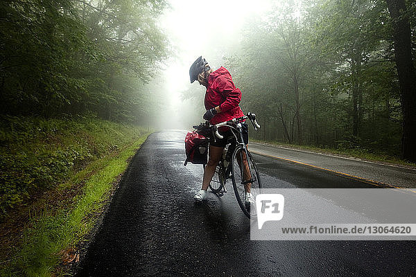 Full length of woman with bicycle on road amidst trees at forest during foggy weather